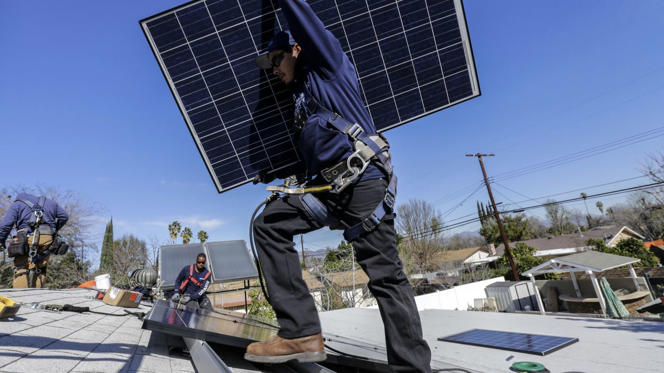 Alejandro DeLeon carries a solar panel as workers from home solar company Sunrun install a system on a home in Van Nuys, California.