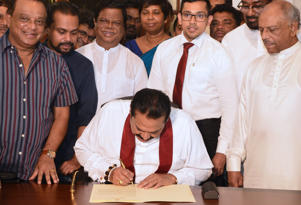 Sri Lankas former president Mahinda Rajapakse (C) signs a document backing down from his controversial appointment as prime minister in Colombo on December 15, 2018. - Sri Lanka's strongman leader Mahinda Rajapakse bowed down on December 15 ending an unprecedented constitutional crisis that sparked international concern in the strategically-placed Indian Ocean nation. (Photo by LAKRUWAN WANNIARACHCHI / AFP)        (Photo credit should read LAKRUWAN WANNIARACHCHI/AFP/Getty Images)