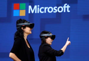 FILE- In this May 11, 2017, file photo, members of a design team at Cirque du Soleil demonstrate use of Microsoft's HoloLens device in helping to virtually design a set at the Microsoft Build 2017 developers conference in Seattle. Microsoft is threatening to overtake Apple as the world's most valuable publicly traded company. The market closed Tuesday, Nov. 27, with Microsoft just behind Apple. (AP Photo/Elaine Thompson, File)