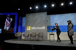 Microsoft Senior Product Marketing Manager Sohana Punithakumar, right, uses a Microsoft HoloLens device to talk to a colleague in a remote location, who is shown as a holographic image on the screen at left, during a demonstration at the annual Microsoft Corp. shareholders meeting, Wednesday, Nov. 28, 2018, in Bellevue, Wash. (AP Photo/Ted S. Warren)