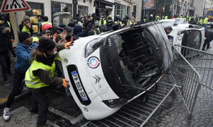 Demonstrators destroy cars during a protest of Yellow vests (Gilets jaunes) against rising oil prices and living costs, near the Champs Elysees in Paris, on December 1, 2018. -