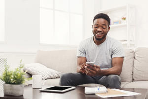 Happy young african-american man at home sending messages on smartphone sitting on beige couch in light livingroom, copy space