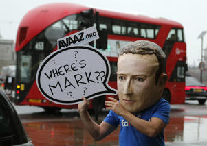 "An activist wearing a Facebook CEO Mark Zuckerberg mask stands outside Portcullis House in Westminster as an international committee of parliamentarians met for a hearing on the impact of disinformation on democracy in London, Tuesday, Nov. 27, 2018. Lawmakers from nine countries grilled a Facebook executive who came in place of Zuckerberg on Tuesday as part of an international hearing at Britain's parliament on disinformation and ""fake news.""  (AP Photo/Frank Augstein)"
