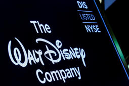 a close up of a sign: A screen shows the trading info for The Walt Disney Company company on the floor of the NYSE in New York