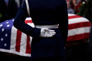 A member of the Air Force stands guard while people pay respects as the remains of former US President George H. W. Bush lie in state in the US Capitol's rotunda Dec. 4, 2018 in Washington.