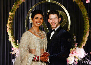 Indian Bollywood actress Priyanka Chopra (L) and US musician Nick Jonas, who were recently married, pose for a photograph during a reception in New Delhi on December 4, 2018. - Bollywood actress Priyanka Chopra and American singer Nick Jonas hosted an extravagant concert on December 2 for their star-studded wedding guests as the couple tied the knot at a lavish Indian palace. (Photo by SAJJAD HUSSAIN / AFP) (Photo credit should read SAJJAD HUSSAIN/AFP/Getty Images)