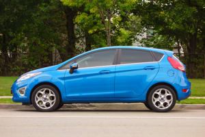 'Hamilton, Canada - September 15, 2013: Side view of a blue colored sixth generation Ford Fiesta compact car parked on the street.'