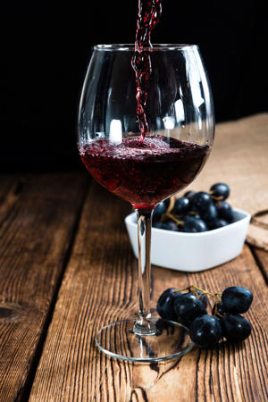 a glass of red wine: Red Wine (on wooden background)