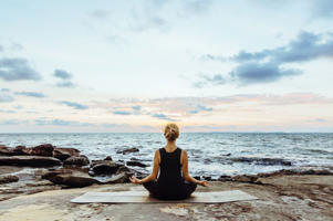 a person sitting at a beach: Young woman performs yoga moves on bluff above sea