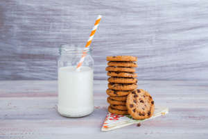 Stack of chocolate chip cookies and jar of milk
