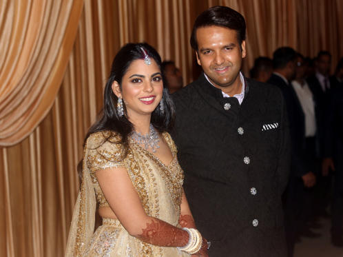 Slide 1 of 40: Isha Ambani, the daughter of the Chairman of Reliance Industries Mukesh Ambani, and her husband Anand Piramal, heir to a real-estate and pharmaceutical business, pose during their wedding reception in Mumbai, India, December 14, 2018. REUTERS/Francis Mascarenhas