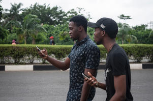 Timi Ajiboye (L) and Tobi Akinnubi (R) use the Pokemon Go application on their mobile on the campus grounds of the University of Lagos on July 14, 2016.  Pokemon Go mania has players armed with smartphones hunting streets, parks, rivers, landmarks and other sites to capture monsters and gather supplies. The free app, based on a Nintendo title that debuted 20 years ago, has been adapted to the mobile internet age by Niantic Labs, a company spun out of Google last year. Pokemon Go uses smartphone satellite location, graphics and camera capabilities to overlay cartoon monsters on real world settings, challenging players to capture and train the creatures for battles.  / AFP / STEFAN HEUNIS        (Photo credit should read STEFAN HEUNIS/AFP/Getty Images)