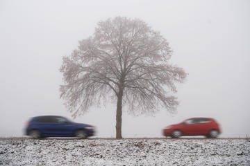 TOPSHOT - Cars drive on a country road through the snowy landscape in Grabenstetten near Reutlingen, southwestern Germany, on November 27, 2018. (Photo by Sebastian Gollnow / dpa / AFP) / Germany OUT        (Photo credit should read SEBASTIAN GOLLNOW/AFP/Getty Images)