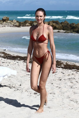 a person standing on a beach: Candice Swanepoel heats up the beach as she relaxes with friends in Miami on Dec. 8.