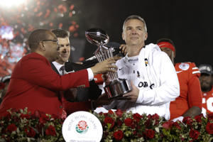 Ohio State coach Urban Meyer, right, holds the trophy after the team's 28-23 win over Washington in the Rose Bowl NCAA college football game Tuesday, Jan. 1, 2019, in Pasadena, Calif. (AP Photo/Jae C. Hong)