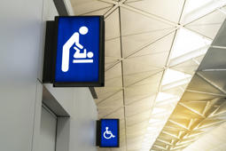 Illuminated signboard for deaper changing rooms and disabled toilet in international airport with copy space for text. Baby changing room sign light box in airport.