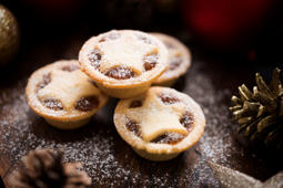 Three small Mince Pies, dusted with icing sugar with Christmas decorations.