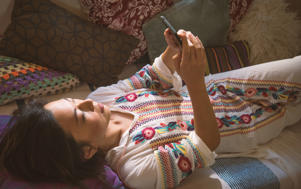 Woman laying down looking at mobile phone (Representative image)