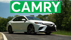 a car parked in front of a sign: 2018 Toyota Camry Road Test