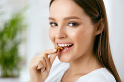 Woman Eating Healthy Diet Food In Kitchen. Beautiful Smiling Young Female Eating Nuts. Healthy Nutrition Concept. High Resolution.
