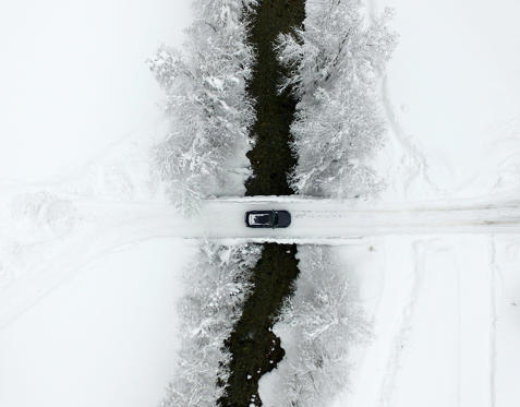 Slide 1 of 56: TOPSHOT - An aerial view shows a car crossing a bridge as the street is snow covered on January 9, 2019 in Untertauern, Austria. (Photo by HELMUT FOHRINGER / APA / AFP) / Austria OUT        (Photo credit should read HELMUT FOHRINGER/AFP/Getty Images)