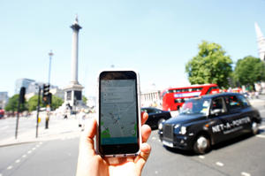 A photo illustration shows the Uber app and a black cab in London, Britain (REUTERS)