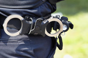 Police officers belt with handcuffs. (Getty Images)