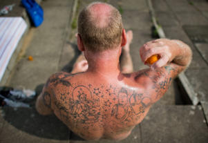 A man sprays suncream on his tatooed body at 'Volksbad Limmer' public pools in Hanover 16 July 2014. Photo: JULIAN STRATENSCHULTE/dpa | usage worldwide   (Photo by Julian Stratenschulte/picture alliance via Getty Images)