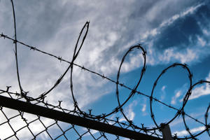 Barbed wire on top of chainlink fence. New York City, USA
