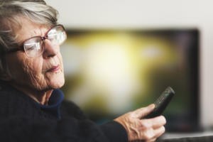 A gray-haired woman in her 70s holds a TV's remote control, peering down at the markings on it but unable to read them clearly.