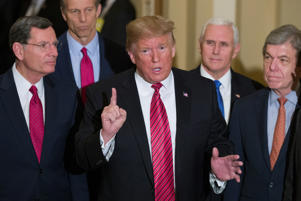 Sen. John Barrasso, R-Wyo., left, and Sen. John Thune, R-S.D., stand with President Donald Trump, Vice President Mike Pence, Sen. Roy Blunt, R-Mo., and Senate Majority Leader Mitch McConnell of Ky., as Trump speaks while departing after a Senate Republican Policy luncheon, on Capitol Hill