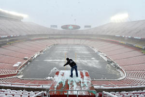 Kyle Haraugh of NFL Films clears snow from a camera location at Arrowhead Stadium before an NFL divisional football playoff game between the Kansas City Chiefs and the Indianapolis Colts, in Kansas City, Mo., Saturday, Jan. 12, 2019. (AP Photo/Ed Zurga)