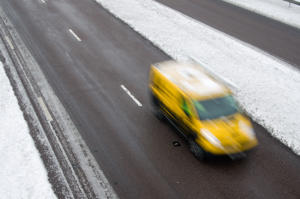 Ashford, UK - February 5, 2012: An AA breakdown vehicle of the Automobile Association (the AA) heads under a motorway bridge. Heavy snow has fallen overnight. Two lanes of the three on the M20 are open. At the top is the exit slip road.