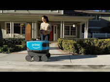 a man standing in front of a building: Amazon Scout is a fully-electric delivery system from Amazon designed to safely get packages to customers using autonomous delivery devices. Learn more: http://amazon.com/scout
