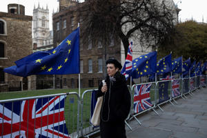 LONDON, ENGLAND - JANUARY 23: A woman walks past EU and Union flags outside the Houses of Parliament on January 23, 2019 in London, England. There are reports that MPs are proposing alternative plans to the Prime Ministers existing Brexit deal, including a possible extension to the exit date, currently scheduled for 29 March. (Photo by Dan Kitwood/Getty Images)