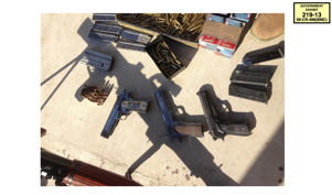 "In this undated photo provided by the United States Attorney's Office for the Eastern District of New York, a cache of weapons and ammunition seized by authorities from the Sinaloa cartel is shown. The first handgun on the left bears the initials of Mexican drug lord Joaquin ""El Chapo"" Guzman. The photo was offered as evidence in Guzman's drug trafficking trial in New York on Thursday, Jan. 17, 2019. (United States Attorney's Office for the Eastern District of New York via AP)"