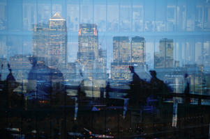 Multiple exposure of city commuters crossing London Bridge and skyscrapers in London
