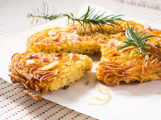 Traditional fried spaghetti pizza of Southern Italy with salami and cheese decorated with rosemary sprigs