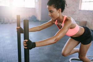 Side view shot of fit young woman pushing the sled at gym. African woman doing intense physical workout in gym.