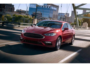 a red car parked on a city street: 2019 Ford Fusion