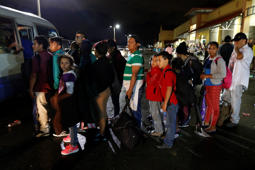 Migrants hoping to reach the U.S. wait in line to board a bus toward Honduras' border with Guatemala, as hundreds of migrants set off by bus or on foot from a main bus station in San Pedro Sula, Honduras, late Monday, Jan. 14, 2019. Yet another caravan of Central American migrants set out Monday from Honduras, seeking to reach the U.S. border following the same route followed by thousands on at least three caravans last year. (AP Photo/Delmer Martinez)