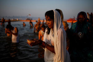 "Devotees pray after taking a holy dip at Sangam, the confluence of the Ganges, Yamuna and Saraswati rivers, during ""Kumbh Mela"", or the Pitcher Festival, in Prayagraj"