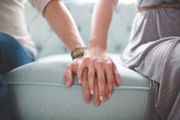 Waist photo of man and woman holding hands while sitting on a couch