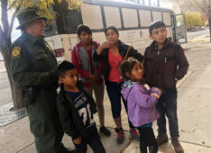 In this Thursday, Nov. 29, 2018 photo, a migrant family from Central America waits outside the Annunciation House shelter in El Paso, Texas, after a U.S. Immigration and Customs Enforcement officer drops them off. Volunteer shelters along the U.S.-Mexico border say they are preparing for an expected surged of new immigrants seeking asylum in the U.S. who will need temporary housing as the holidays approach. (AP Photo/Russell Contreras)