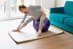 Pregnant woman exercising on fitness ball
