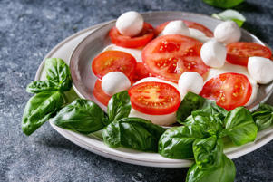 Italian caprese salad with sliced tomatoes, mozzarella cheese, basil, olive oil. Served in ceramic plate over gray texture background. Close up. (Photo by: Natasha Breen/REDA&CO/UIG via Getty Images)