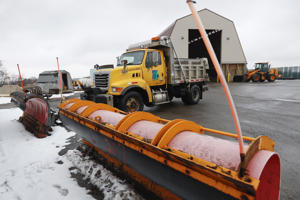 A Pennsylvania Department of Transportation road treatment truck pulls in to attach a plow at a storage facility in Franklin Park, Pa. on Friday, Jan. 18, 2019. Weather forecasters are are predicting a heavy weekend snow storm across Pennsylvania and surrounding states.