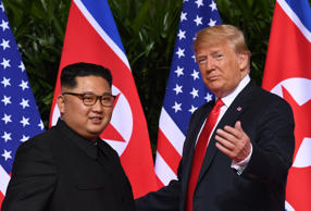 US President Donald Trump (R) gestures as he meets with North Korea's leader Kim Jong Un (L) at the start of their historic US-North Korea summit, at the Capella Hotel on Sentosa island in Singapore on June 12, 2018. - Donald Trump and Kim Jong Un have become on June 12 the first sitting US and North Korean leaders to meet, shake hands and negotiate to end a decades-old nuclear stand-off. (Photo by SAUL LOEB / AFP)        (Photo credit should read SAUL LOEB/AFP/Getty Images)