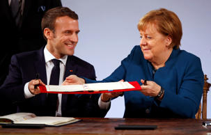 German Chancellor Angela Merkel and French President Emmanuel Macron sign a new agreement on bilateral cooperation and integration, known as Treaty of Aachen, in Aachen, Germany, January 22, 2019.