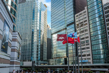 EXCHANGE SQUARE, CENTRAL, HONG KONG SAR, CHINA - 2018/08/09: Flags flutter next to the Hong Kong stock exchange, surrounded by glass-fronted skyscrapers. (Photo by Stefan Irvine/LightRocket via Getty Images)